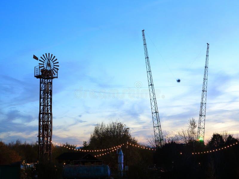 Parque de diversões com passeio do tiro do céu no crepúsculo imagens de stock royalty free