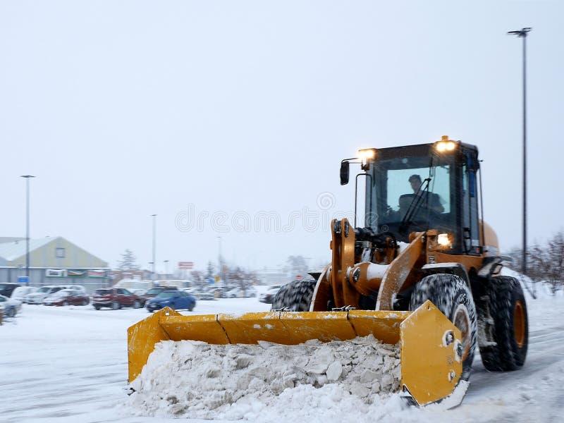 Parque de estacionamento de cancelamento da máquina da remoção de neve durante a tempestade da neve foto de stock royalty free