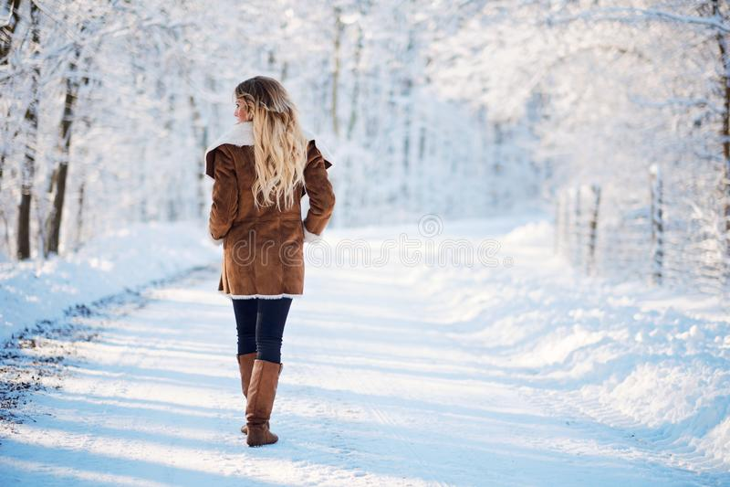 Parque de passeio do inverno da mulher loura nova fotografia de stock royalty free
