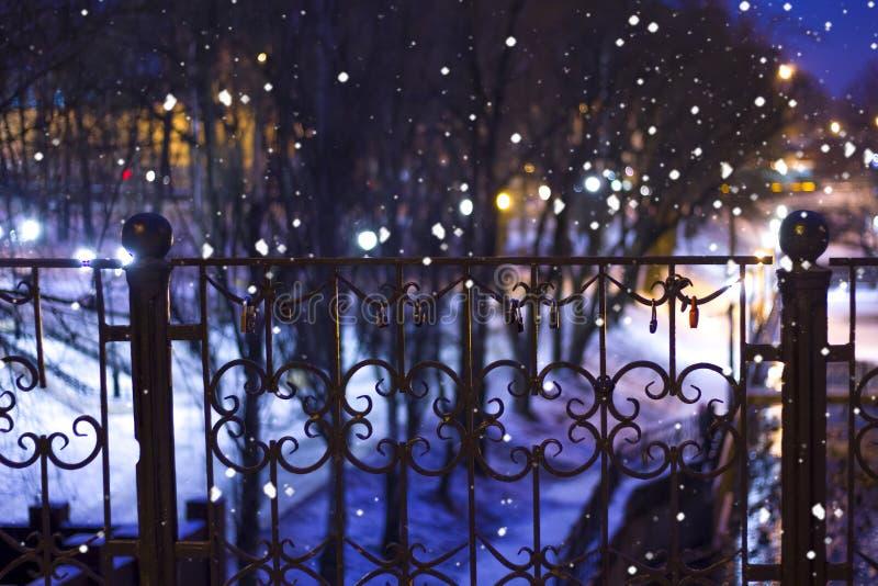 Parque del invierno de la noche con las luces y el candado de la ciudad en la verja nevadas foto de archivo libre de regalías