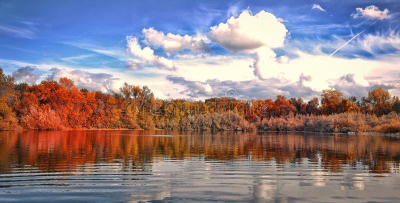 Parque do outono pelo lago Céu azul foto de stock