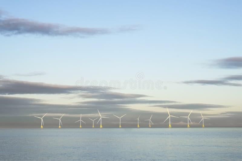 Parque eólico en turbinas flotantes del océano de Mar del Norte en horizonte a poca distancia de la costa en Aberdeen para genera fotos de archivo libres de regalías