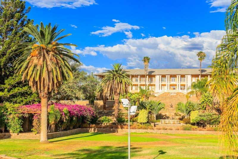 Parque e jardim com a construção amarela escondida atrás das palmas altas, Windhoek do palácio, Namíbia fotos de stock
