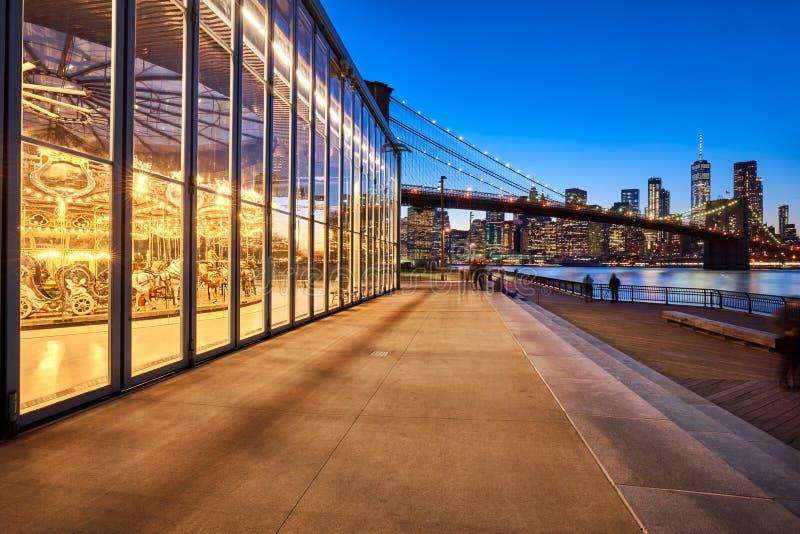 Parque en el crepúsculo con la opinión sobre los rascacielos del Lower Manhattan, el puente del puente de Brooklyn de Brooklyn Ne foto de archivo libre de regalías