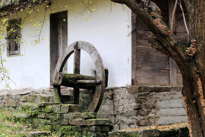 Parque en Ucrania Una casa vieja y una rueda vieja del molino de viento que bombea el agua imagen de archivo libre de regalías