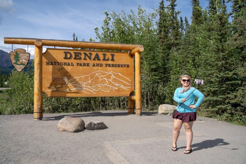 PARQUE NACIONAL ALASKA DE DENALI: Una mujer turística rubia utiliza un palillo del selfie para tomar una foto para los medios soc imagen de archivo