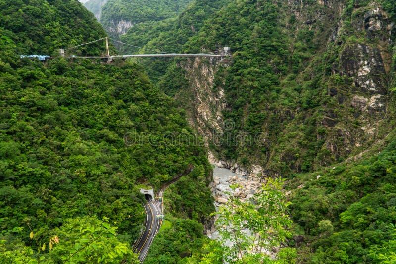 Parque nacional do desfiladeiro de Taroko em Taiwan Montes verdes bonitos cobertos com a folha luxúria com túnel e ponte de suspe imagens de stock