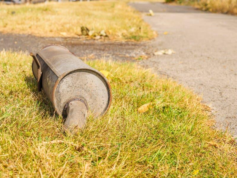 Parque oxidado velho quebrado da tubulação de exaustão que coloca na grama ao lado da estrada britânica foto de stock