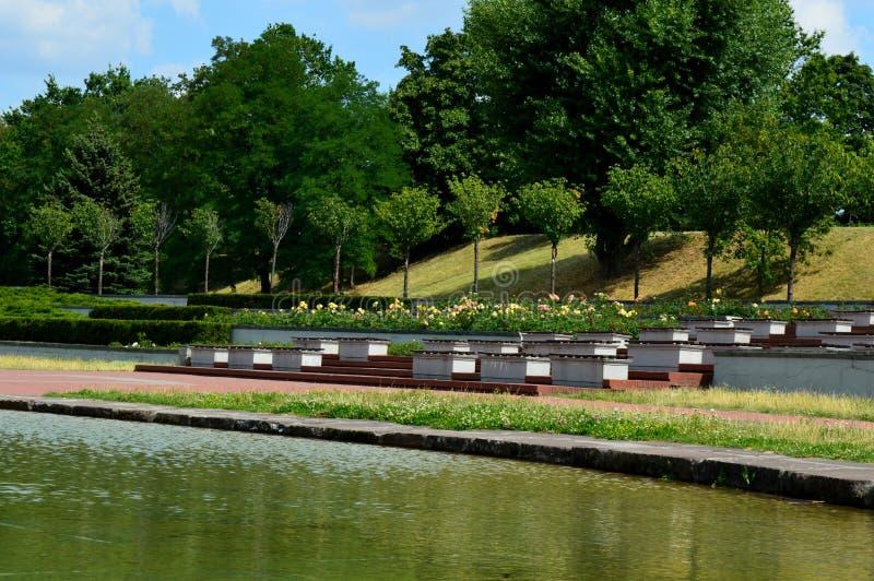 Parque público con una charca y bancos concretos foto de archivo