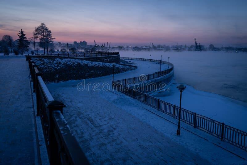 Parque pequeno perto do rio de Angara na cidade de Irkutsk na estação do inverno no por do sol, Sibéria, Rússia imagem de stock
