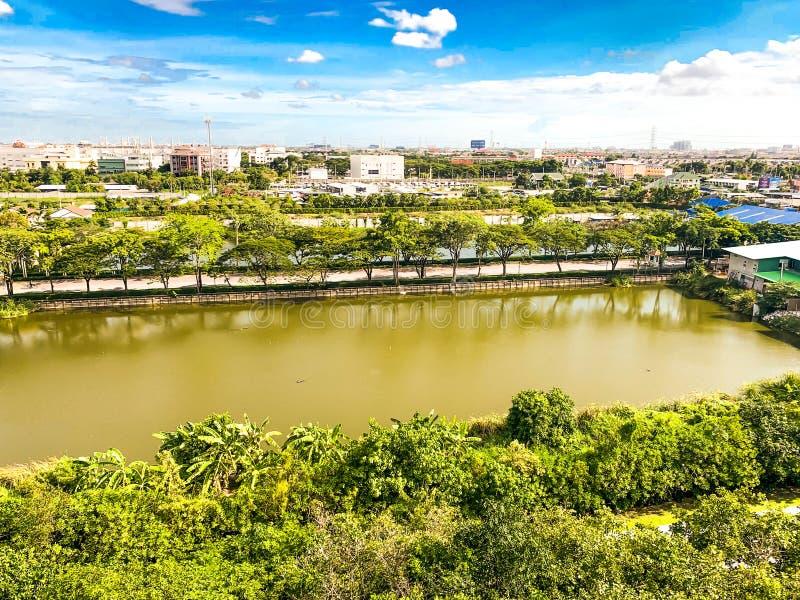 Parque verde, bairro social, grande lagoa e céu azul imagem de stock