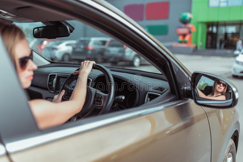 Parquean a una muchacha que conduce un coche de la conducción a la derecha en un estacionamiento, cerca de un centro comercial, t fotografía de archivo