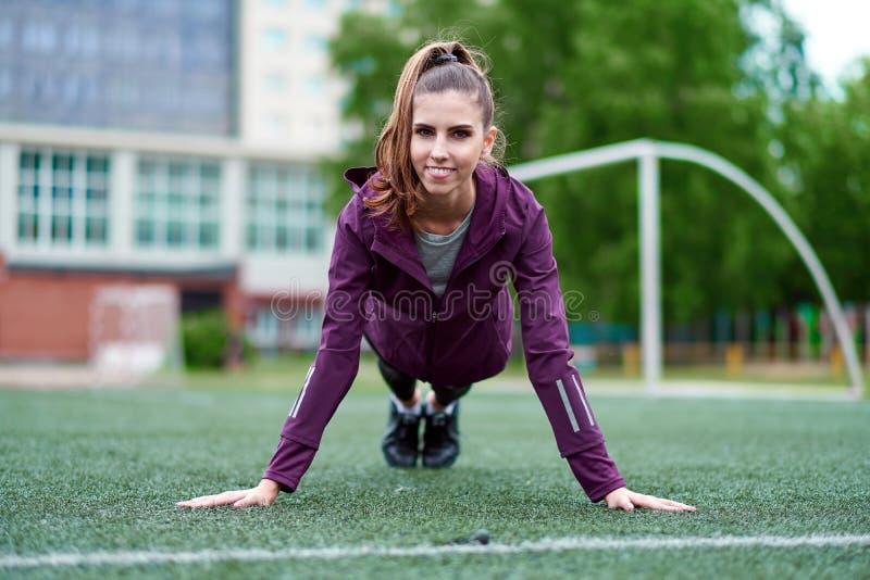 Parquet de femme de forme physique faisant l'exercice de poids du corps pour la formation de force de noyau photographie stock libre de droits