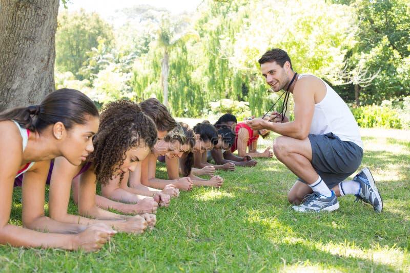 Parquet de groupe de forme physique en parc avec l'entraîneur image libre de droits