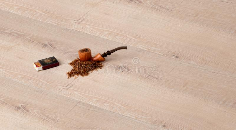 Parquet flooring with pipe, tobacco and matches stock photography