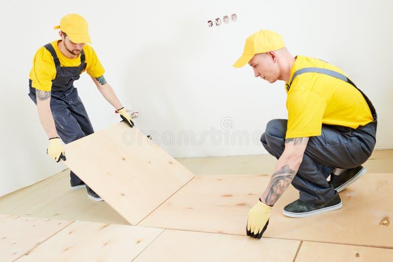 Parqueter le travail installation de contreplaqué à la préparation pour le plancher de parquet en bois photographie stock libre de droits
