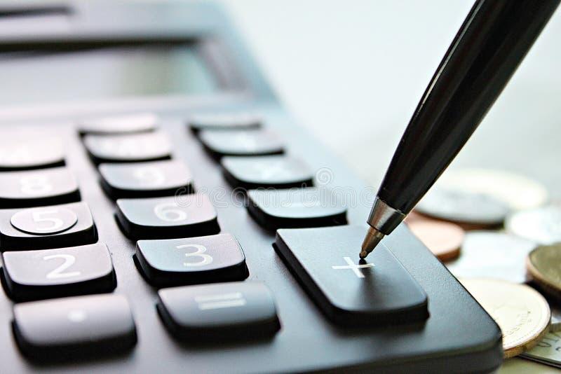 Parquez la presse sur la calculatrice plus de bouton et les pièces de monnaie sur la table de bureau image stock