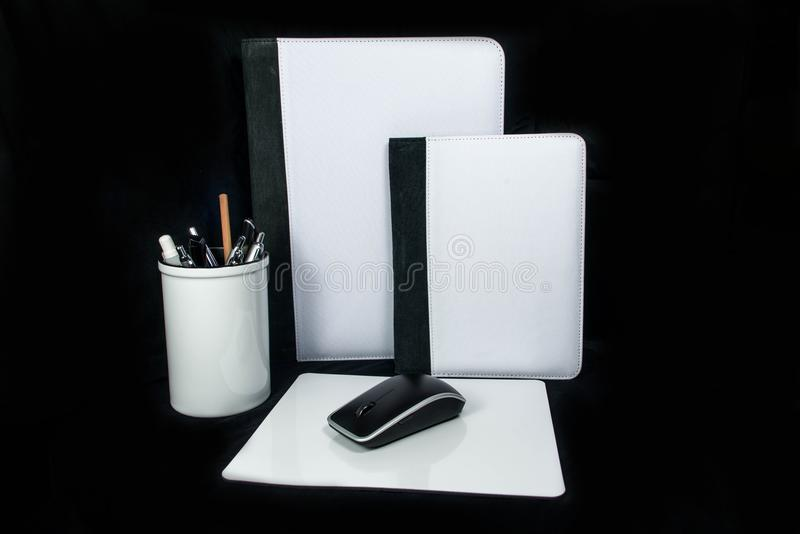 Parquez la tasse, la couverture de carnet de bureau de crayon et le mousepad réglés de tapis de souris sur le fond noir pour la c images stock