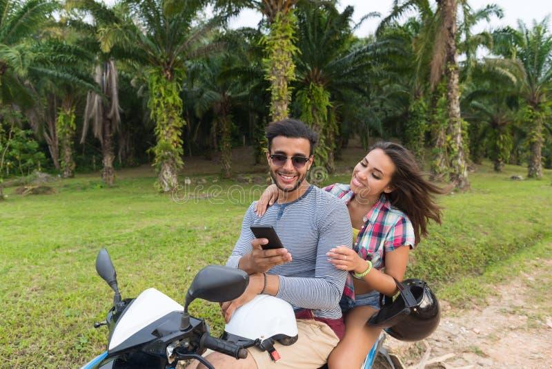 Parridningmoped, ung man och kvinna som använder lopp för cellSmart telefon på cykeln på tropiska Forest Road royaltyfri bild