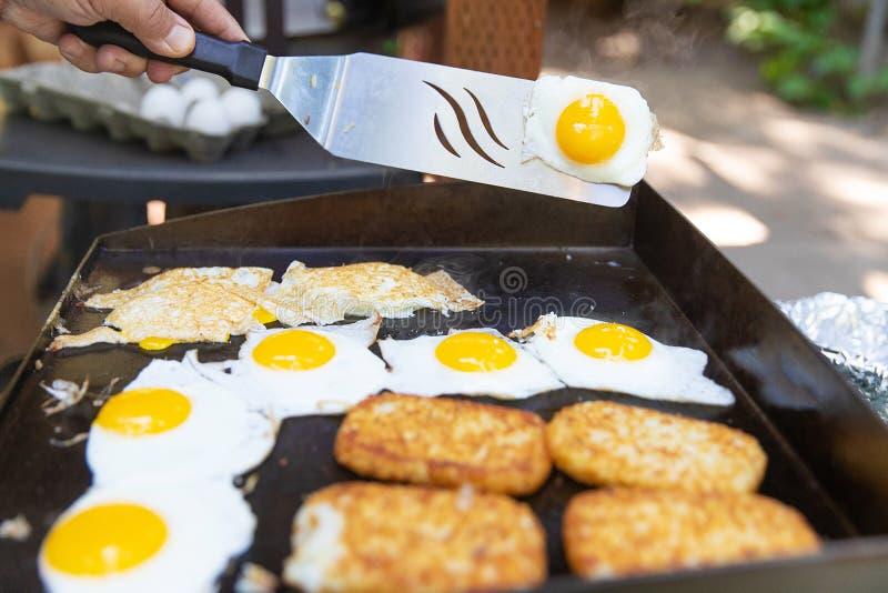 Parrilla al aire libre con los huevos y las papitas fritas para el desayuno imagen de archivo