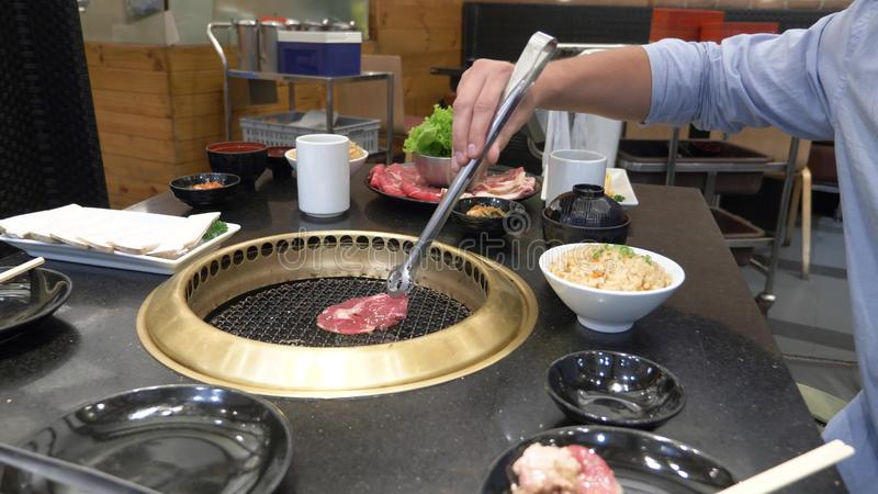 Parrilla coreana de la barbacoa la gente cocina y come los platos cocinados en una parrilla coreana en un restaurante Primer imagenes de archivo
