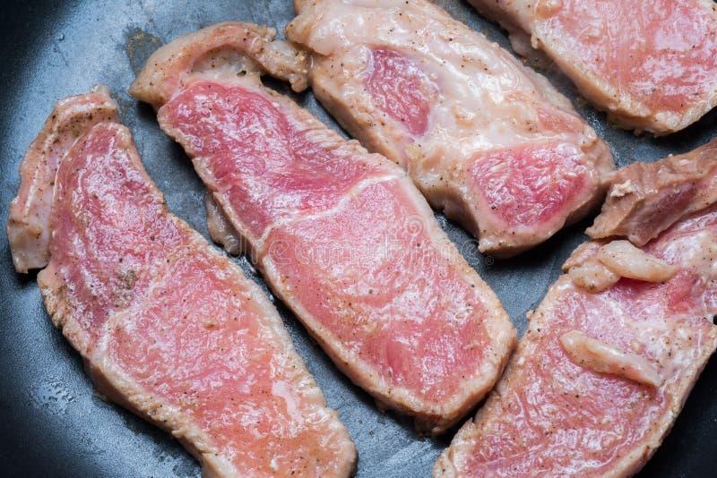 Parrilla cortada cruda del cerdo en la cacerola foto de archivo