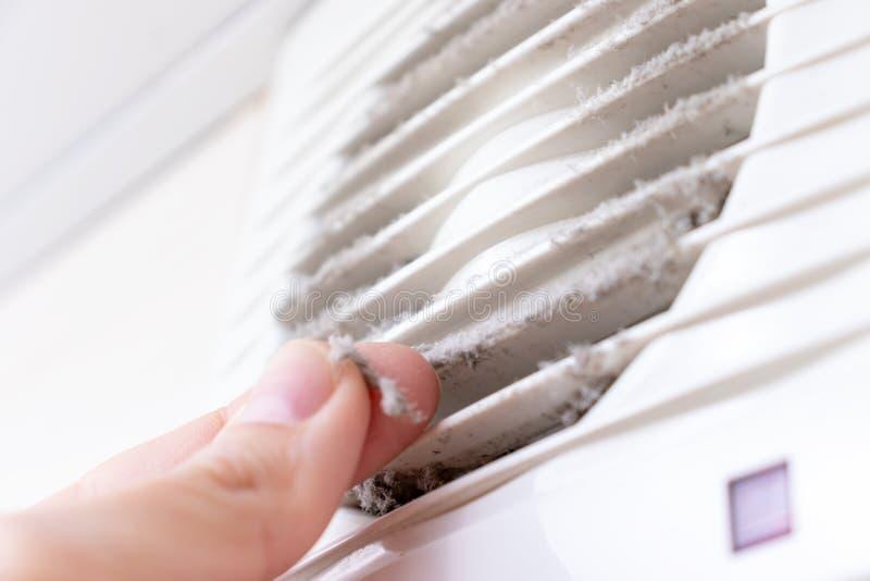 Parrilla de aire plástica blanca extremadamente sucia y polvorienta de la ventilación en casa cercana para arriba y una mano que  fotografía de archivo libre de regalías