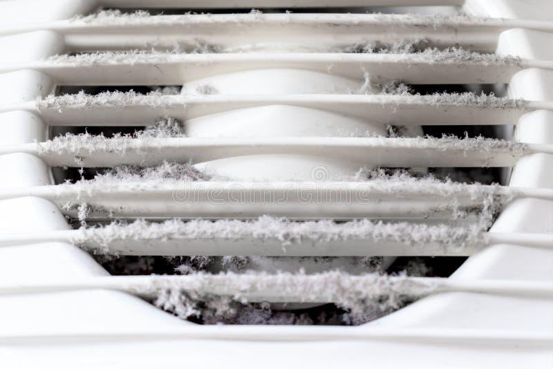 Parrilla de aire pl?stica blanca extremadamente sucia y polvorienta de la ventilaci?n en casa cerca para arriba, da?ino para la s imagenes de archivo