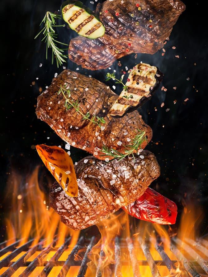 Parrilla de la caldera con las briquetas calientes, la rejilla del arrabio y los filetes de carne de vaca sabrosos volando en el  fotografía de archivo