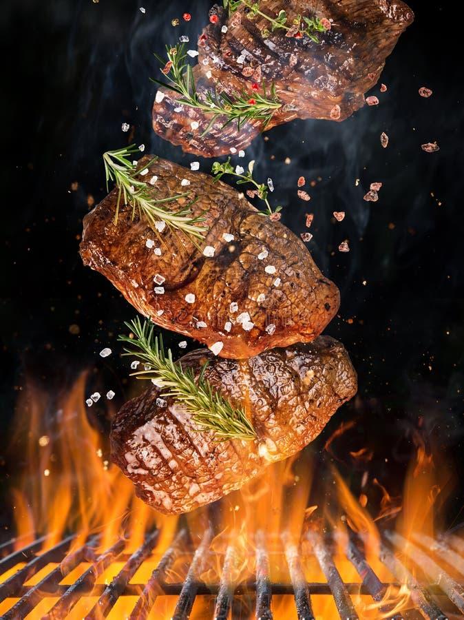 Parrilla de la caldera con las briquetas calientes, la rejilla del arrabio y los filetes de carne de vaca sabrosos volando en el  imagenes de archivo