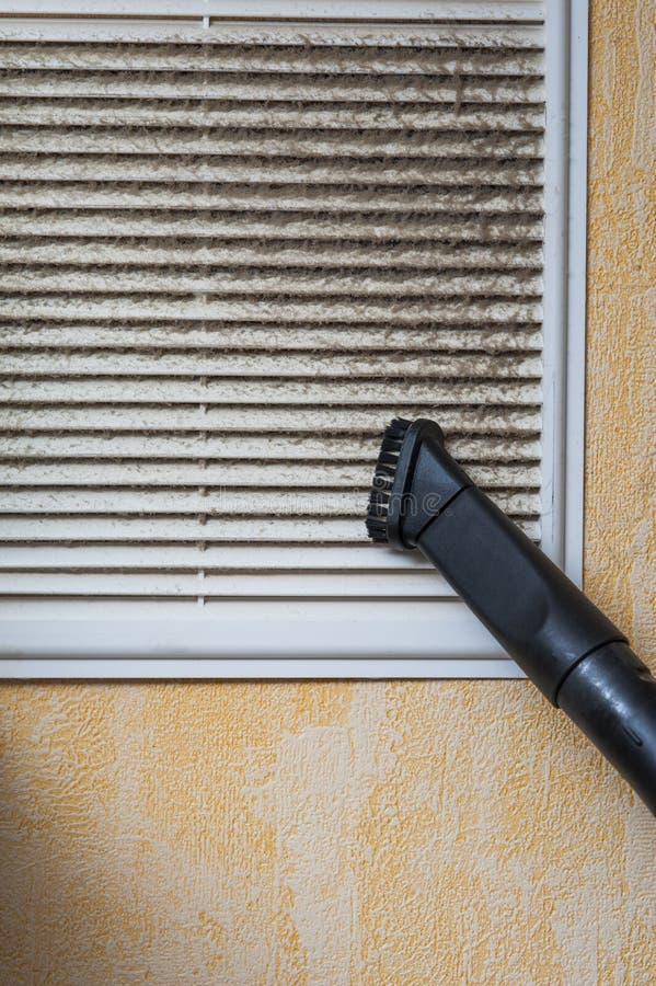 Parrilla de la ventilación de la limpieza con el aspirador fotos de archivo libres de regalías