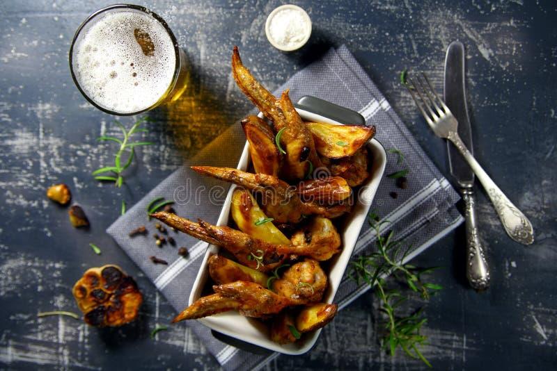 Parrilla de las alas de pollo con las patatas y la cerveza fotografía de archivo libre de regalías