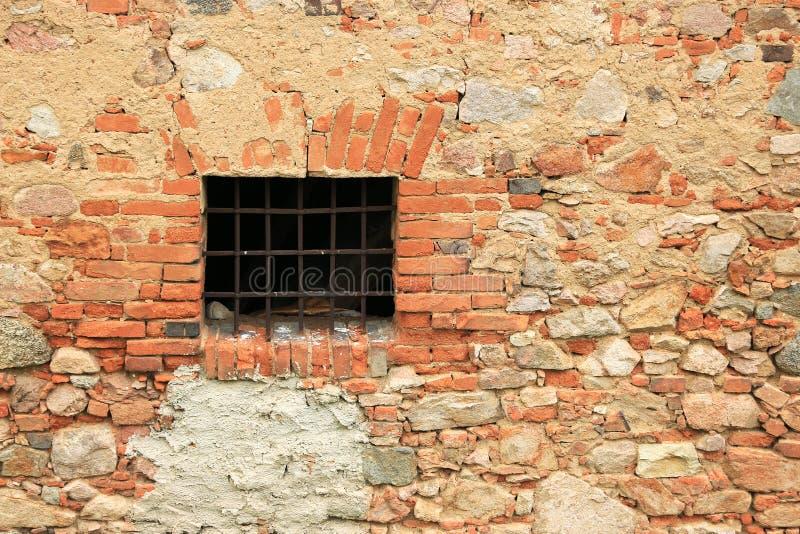 Parrilla de ventana oxidada y pared de ladrillo vieja fotos de archivo libres de regalías