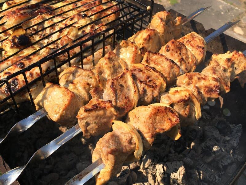 Parrilla en los carbones con el humo, barbacoa Pedazos de carne del pollo asados a la parrilla en la parrilla imágenes de archivo libres de regalías