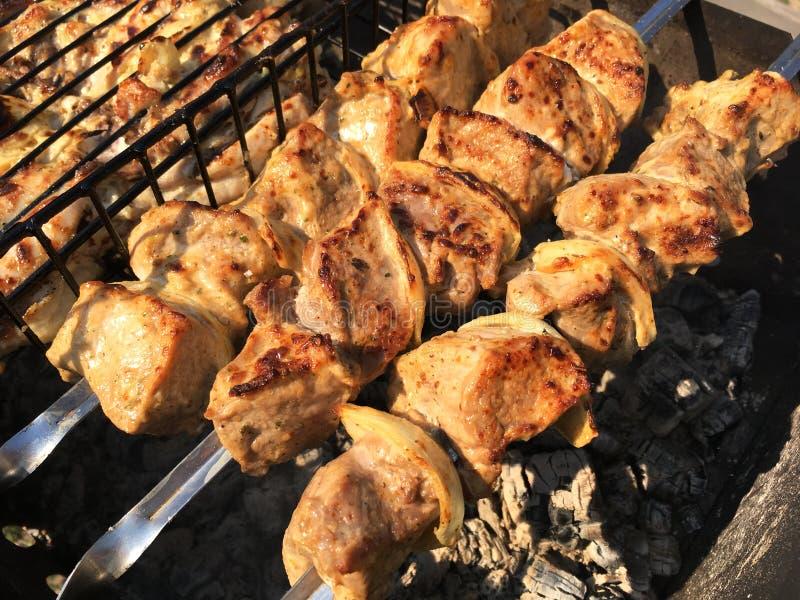 Parrilla en los carbones con el humo, barbacoa Pedazos de carne del pollo asados a la parrilla en la parrilla imagen de archivo