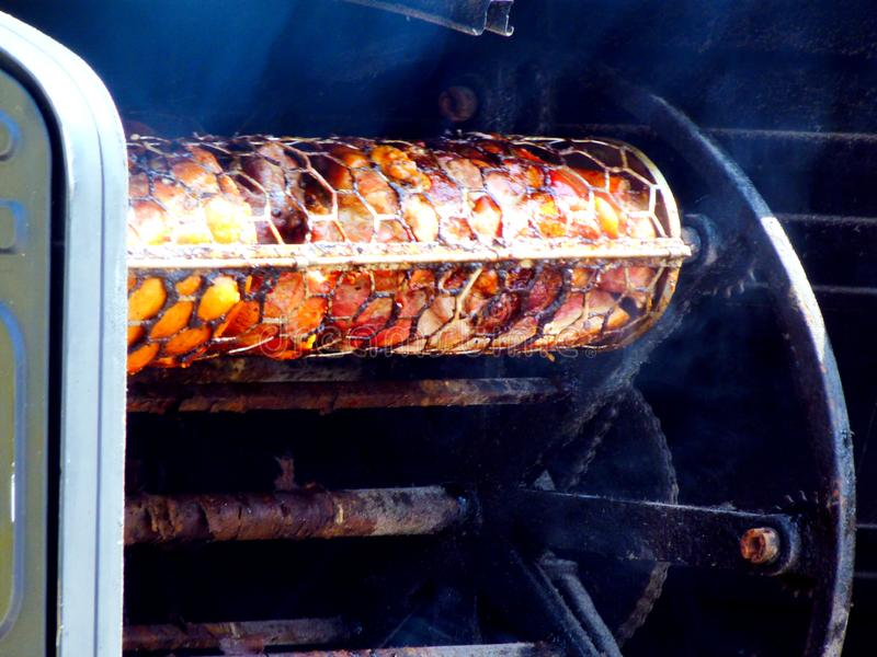 Parrilla giratoria industrial de la carne con las ruedas grandes, la cadena y los tambores de la malla metálica para guardar la r imagen de archivo