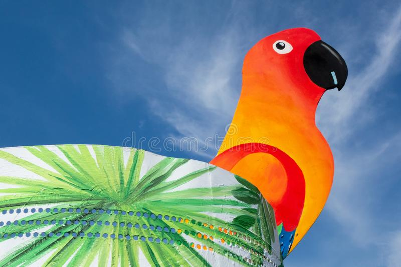 Parrot bird sits on glass edge like cocktail decoration on blue sky background. Vivid vibrant hued colors with copy space. Concept royalty free stock photography