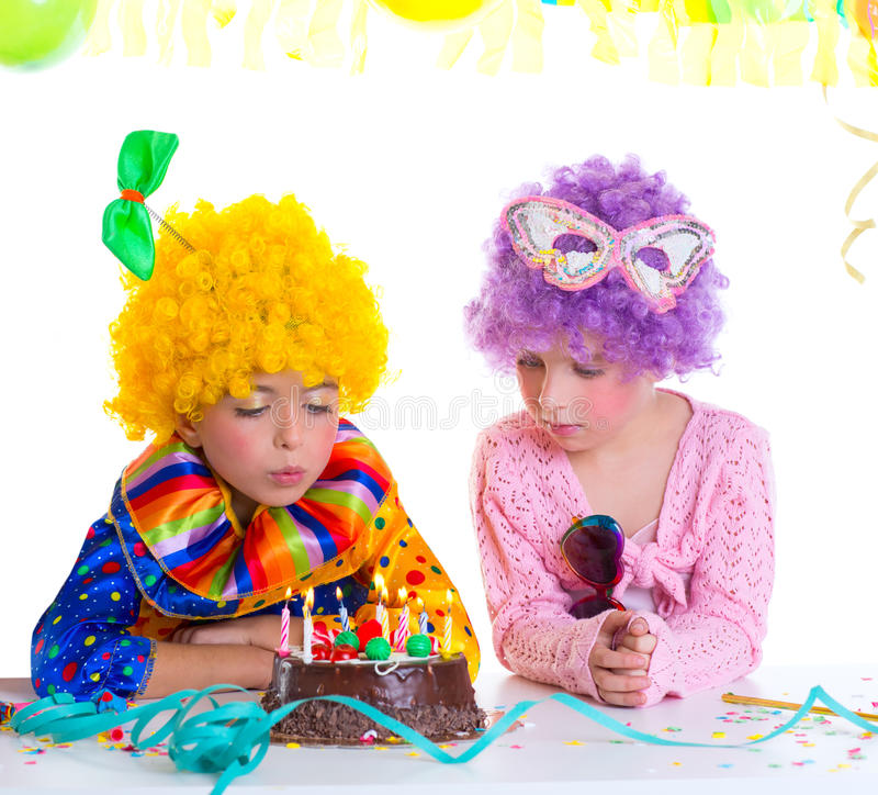 Parrucche del pagliaccio della festa di compleanno dei bambini che soffiano le candele del dolce immagini stock