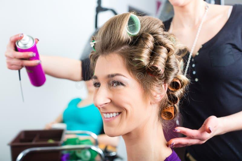 Parrucchiere - capelli d'arricciatura dello stilista di capelli fotografie stock