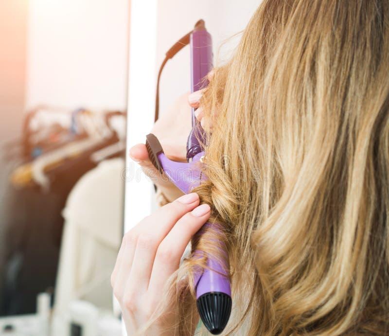 Parrucchiere che arriccia i capelli biondi della donna con le tenaglie del bigodino del ferro da stiro immagine stock libera da diritti