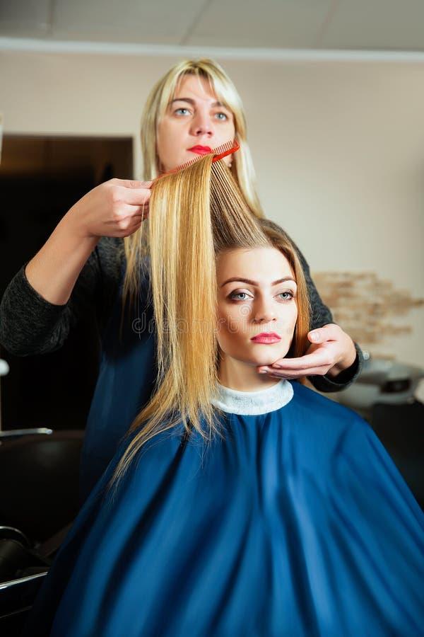 Parrucchiere che fa acconciatura con la spazzola per i capelli fotografia stock libera da diritti