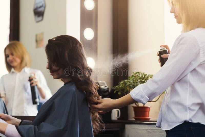 Parrucchiere che fa acconciatura riccia al salone di bellezza immagini stock
