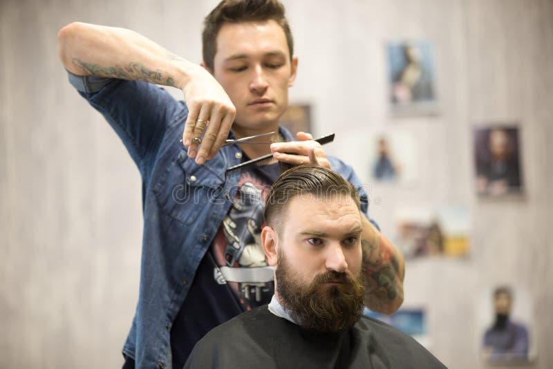 Parrucchiere che fa taglio di capelli per il cliente maschio fotografia stock libera da diritti