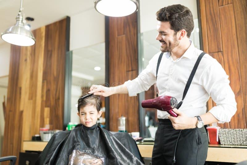 Parrucchiere che pettina capelli del ragazzo in Barber Shop fotografia stock