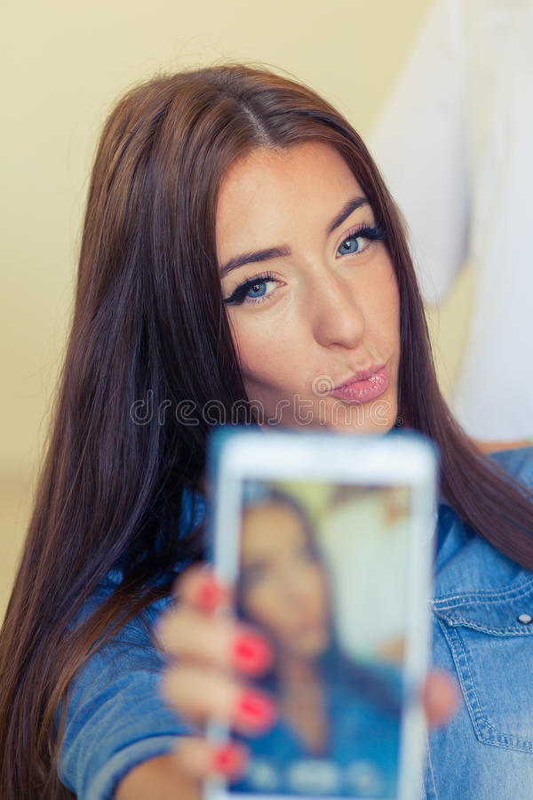 Parrucchiere che pettina la donna dei capelli con il telefono cellulare nel lavoro di parrucchiere immagine stock