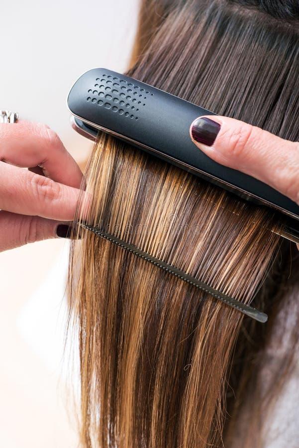 Parrucchiere che raddrizza i capelli di un cliente fotografie stock libere da diritti