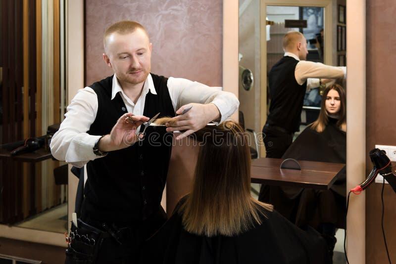 Parrucchiere che sistema capelli marroni con le forbici immagine stock