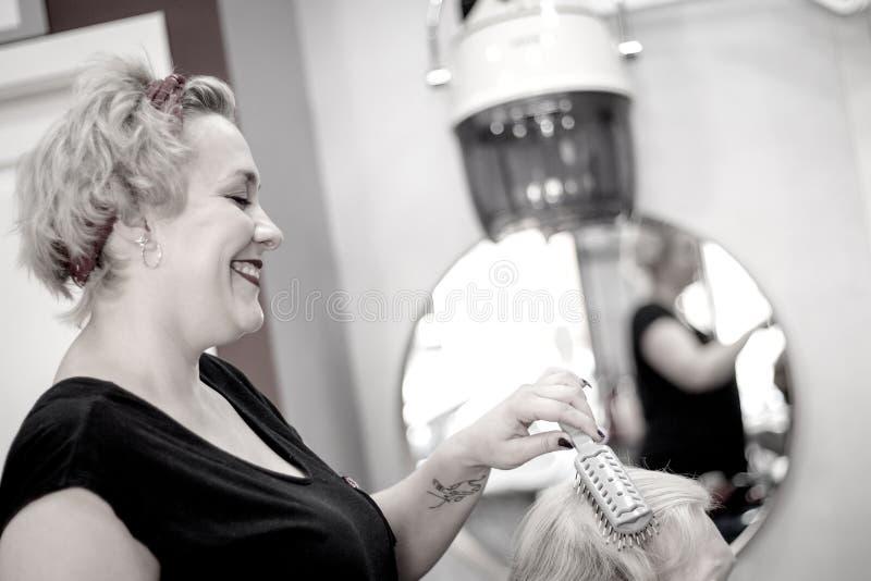 Parrucchiere che spazzola i capelli dei clienti fotografia stock libera da diritti
