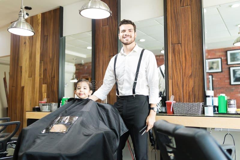 Parrucchiere che sta cliente vicino che si siede per il taglio di capelli al negozio immagini stock