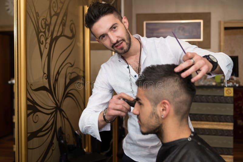 Parrucchiere Cleaning Young Man dopo taglio di capelli immagine stock